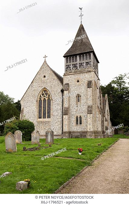 exterior of Saint Peter's church Ovington showing traditional wooden tower, belfry with churchyard and gravestones