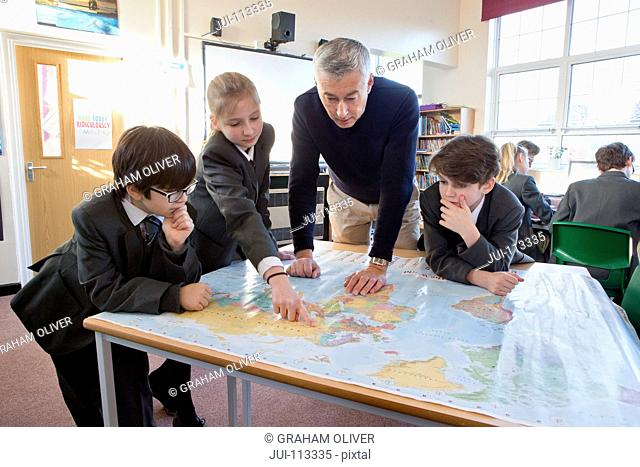 Geography teacher and middle school students using map in classroom