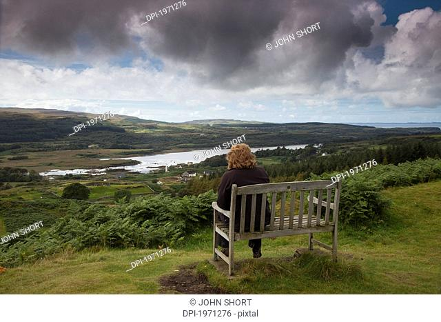 a woman sits on a wooden bench overlooking a landscape, isle of mull scotland