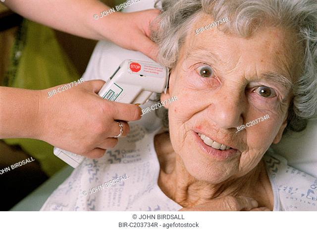 Elderly female patient having temperature checked using a Tympanic thermometer