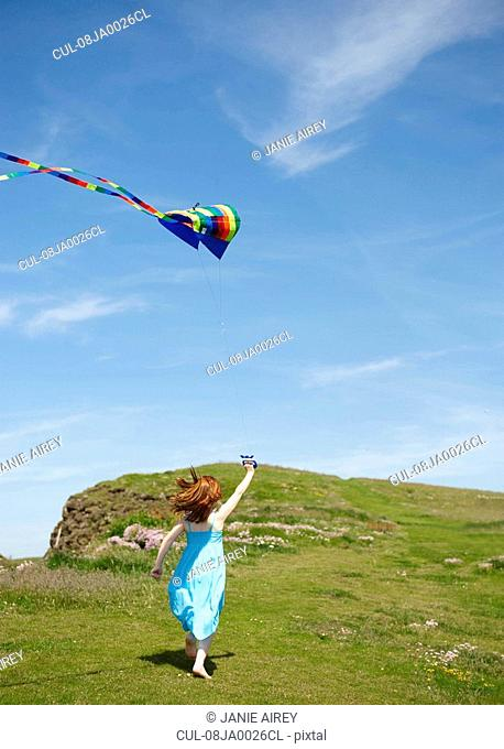 Girl running with kites in field
