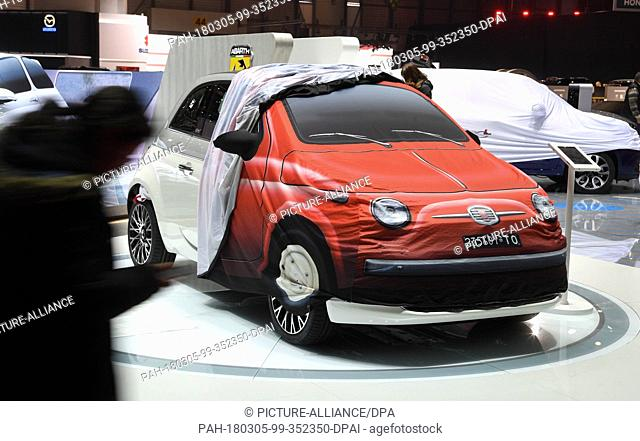 05 March 2018, Switzerland, Geneva: A partly covered Abarth at a fair stand on the previous day of the Geneva Motor Show's press days