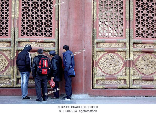 Visitors study the decoration details of the gate of a hall in Forbidden City  Beijing  China