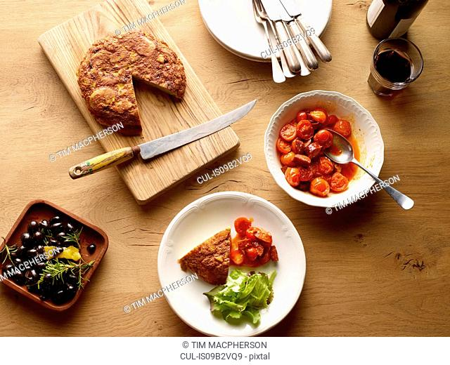 Overhead view of table with Spanish potato tortilla and bowl tomatoes and chorizo