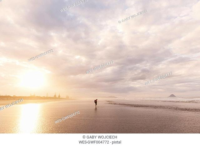 New Zealand, North Island, Bay of Plenty, Ohope Beach, man watching ocean waves, South Pacific Ocean