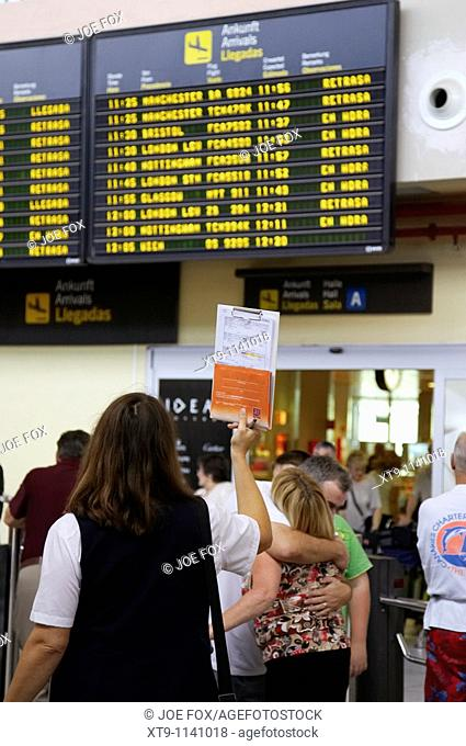 spanish female tour guide waits in front of arrivals message board with list of passengers at Reina Sofia Sur TFS South Airport Tenerife Canary Islands Spain