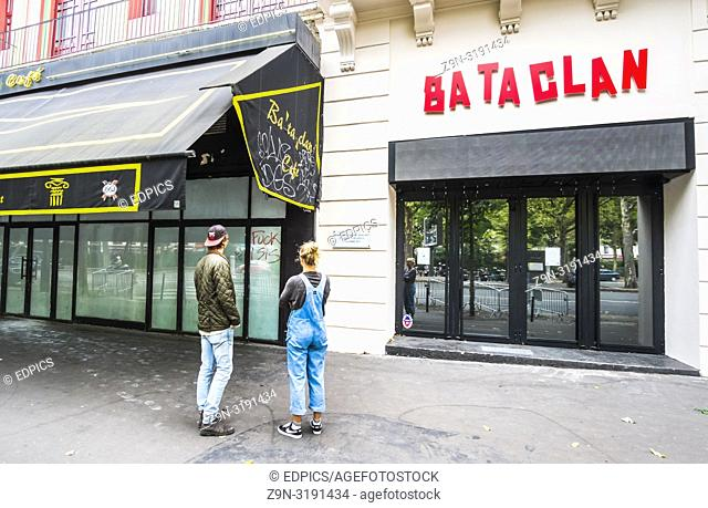 young couple looking at memorial plaque of bataclan terrorist attack, paris, ile de france, france