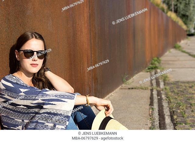 Young woman suns herself outside, semi-portrait