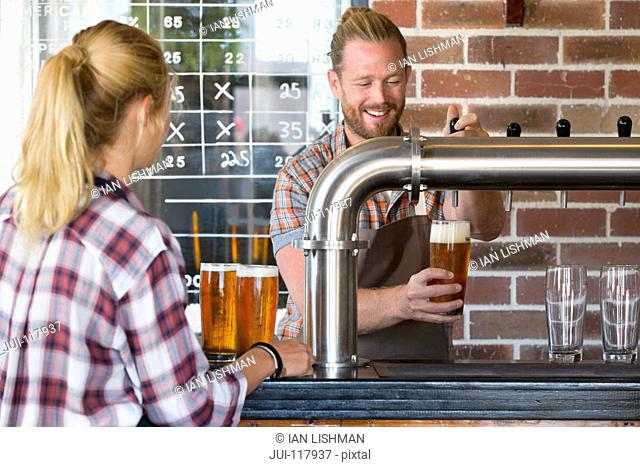Barman In Pub Pouring Pint Of Beer For Waitress In Pub