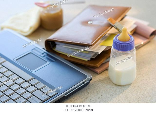 Laptop, planner and baby bottle on table