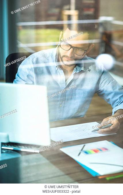 Young man behind windowpane working at computer