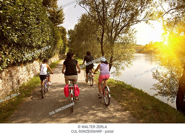Family riding bicycles by river bank