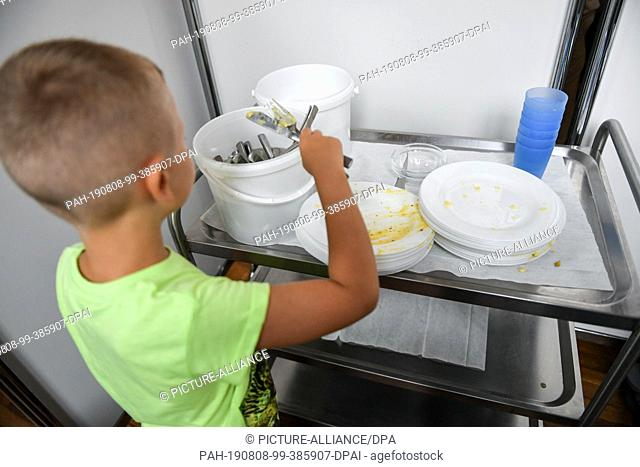 07 August 2019, Berlin: After lunch, a student places used cutlery in a bucket provided on a serving trolley. Photo: Jens Kalaene/dpa-Zentralbild/ZB