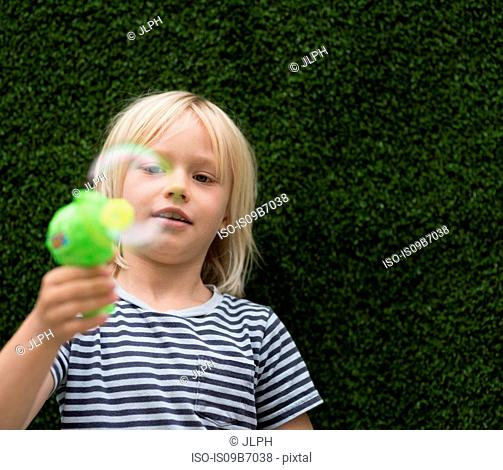 Boy blowing bubble with bubble maker