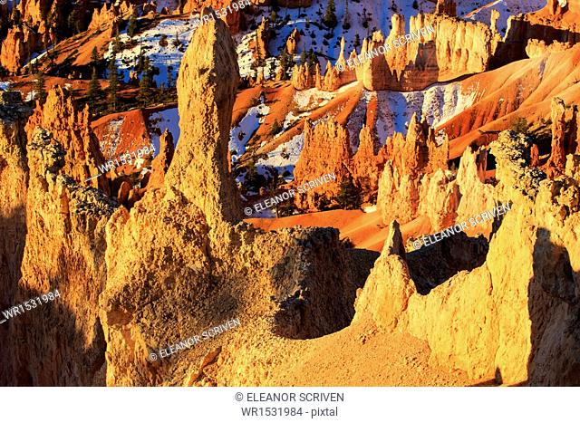 Hoodoos and snow lit by strong dawn light in winter, Queen's Garden Trail at Sunrise Point, Bryce Canyon National Park, Utah, United States of America