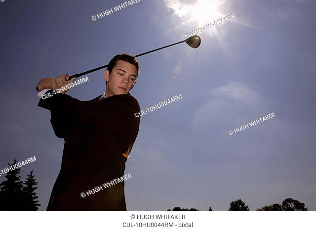 Man in business suit playing golf