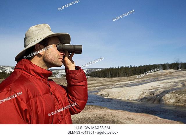 Tourist looking through binoculars, Yellowstone National Park, USA