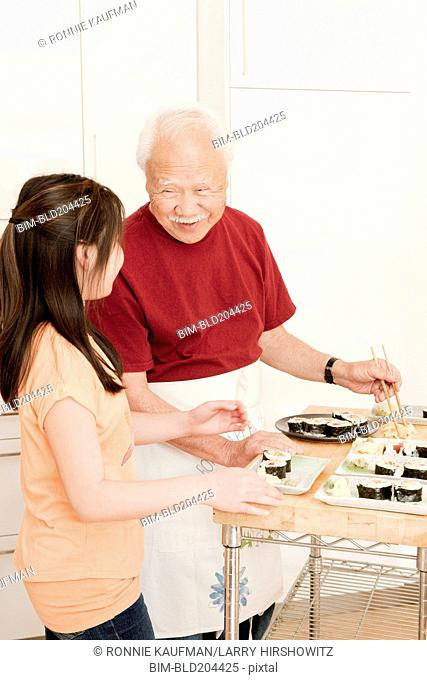 Japanese man and granddaughter cooking in kitchen