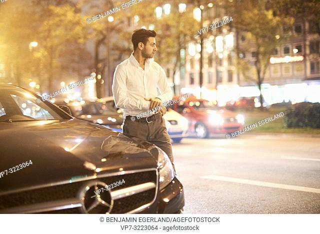 young confident man walking on street in front of car traffic in city at night, Afghan ethnicity, Mercedes Benz, in Munich, Germany