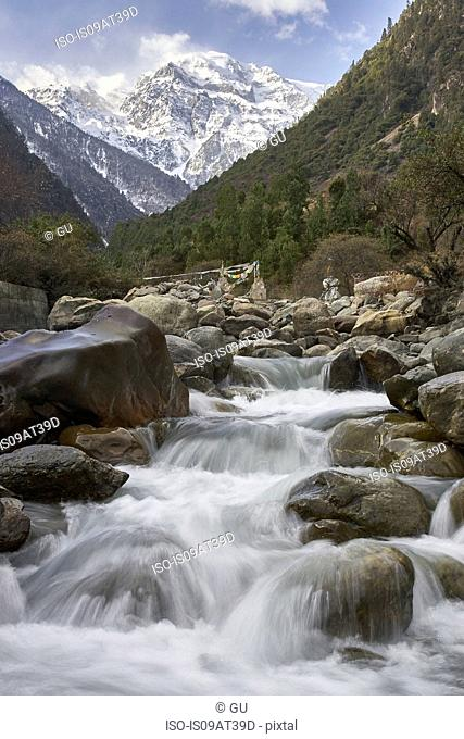Water running down river from snow covered mountain, Shangri-la County, Yunnan, China