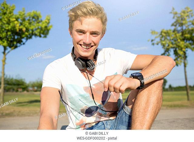 Germany, North Rhine-Westphalia, Oberhausen, Portrait of young man with head phones, smiling