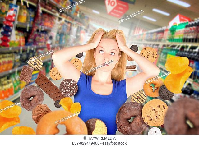 A woman has sweet food snacks around her on in a grocery store. She has fear and there are donuts and cookies. Use it for a health or diet concept