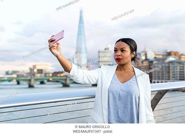 UK, London, woman standing on a bridge taking a selfie
