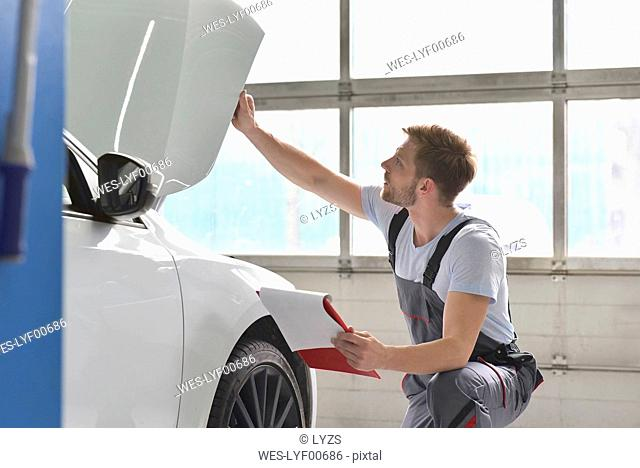 Car mechanic in a workshop examining car