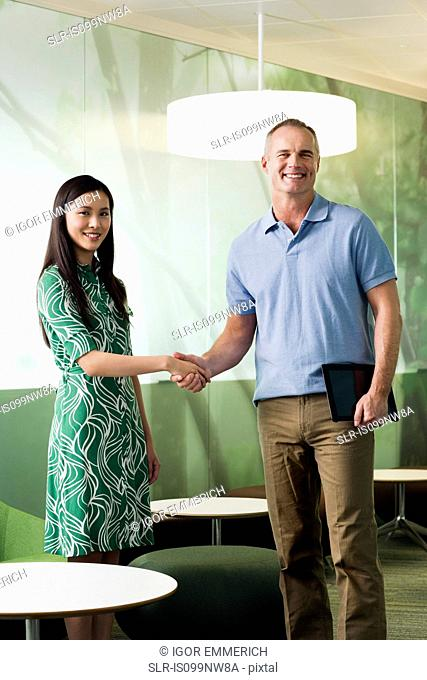 Mature man shaking hands with young woman in meeting