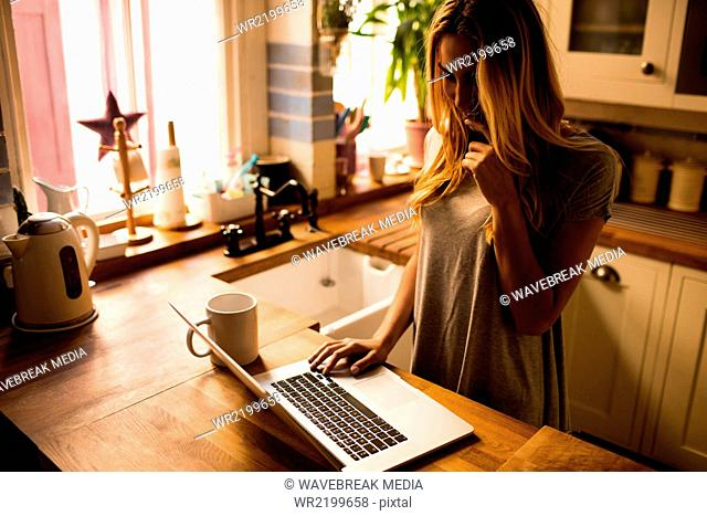 Pretty woman using laptop in the kitchen