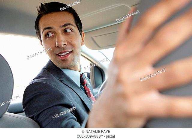 Businessman in car, looking over shoulder