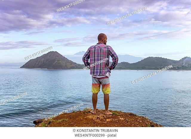Indonesia, Sumbawa island, Young man standing on viewpoint