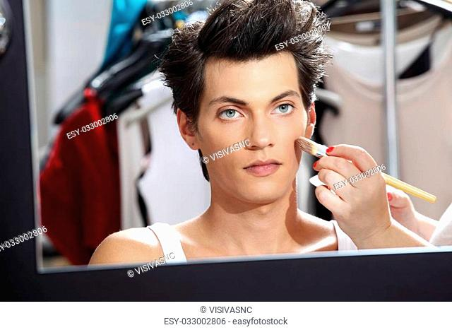 makeup artist applying foundation with a brush, man in the dressing room mirror