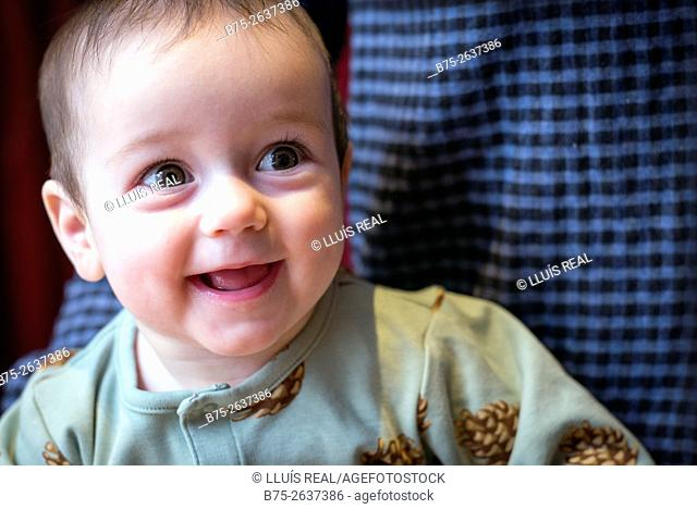 Portrait of a six month old baby girl laughing