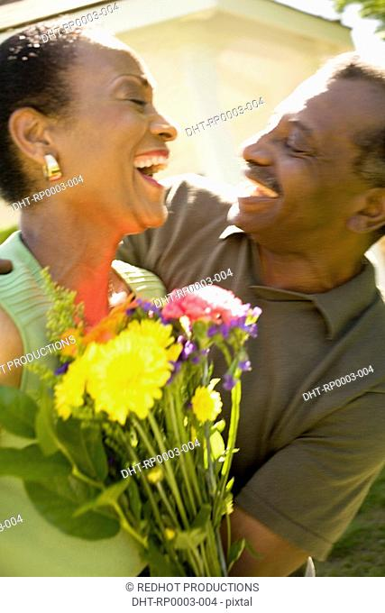A couple with flowers outdoors