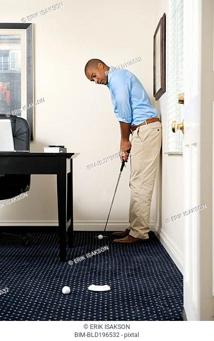 African American businessman putting golf ball