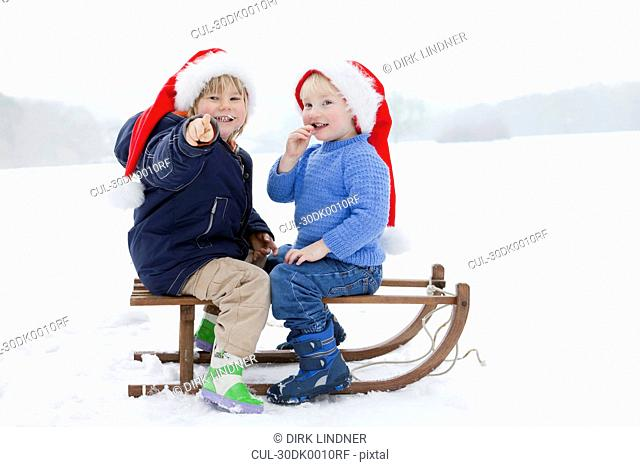 Two boys on a sledge wearing Xmas hats
