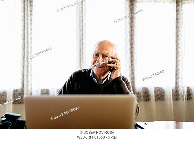 Portrait of smiling senior man on the phone at home