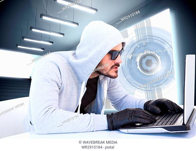 Criminal in hood on laptop in front of interface