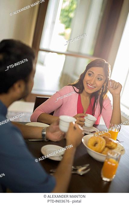 Woman in pink smiling at man at dining table