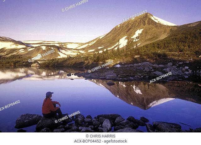 Hiking sitting near alpine lake, Tweedsmuir Park, British Columbia, Canada