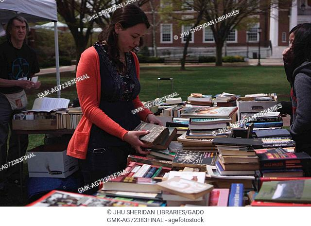 College students and members of the Johns Hopkins and Baltimore communities look through books that have been set up by a vendor for Spring Fair