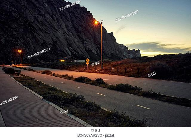 Silhouetted view of Morro Bay Rock and coast road at dusk, Morro Bay, California, USA
