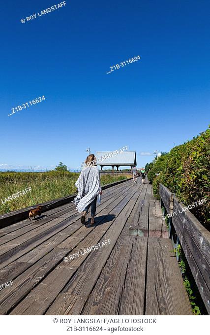 People walking along the wooden boardwalk alongside the Fraser River in Steveston, British Columbia