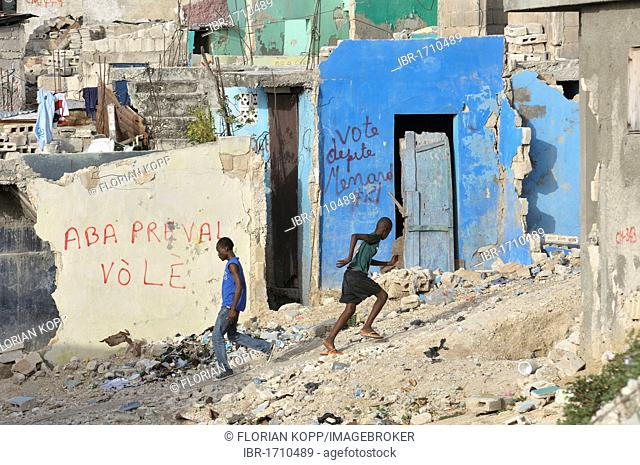 Young men in front of house ruins with graffiti campaigning for the elections in November 2010, slums of Fort National, the district was largely destroyed by...