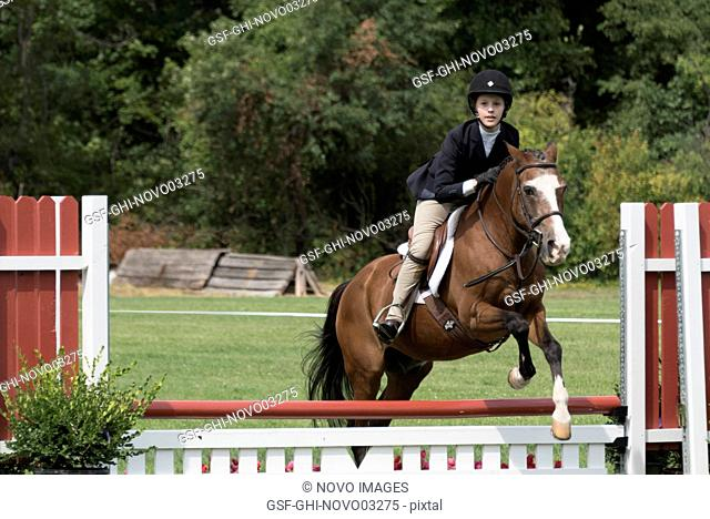Teenage Girl Competitive Rider on Horse Jumping at Show