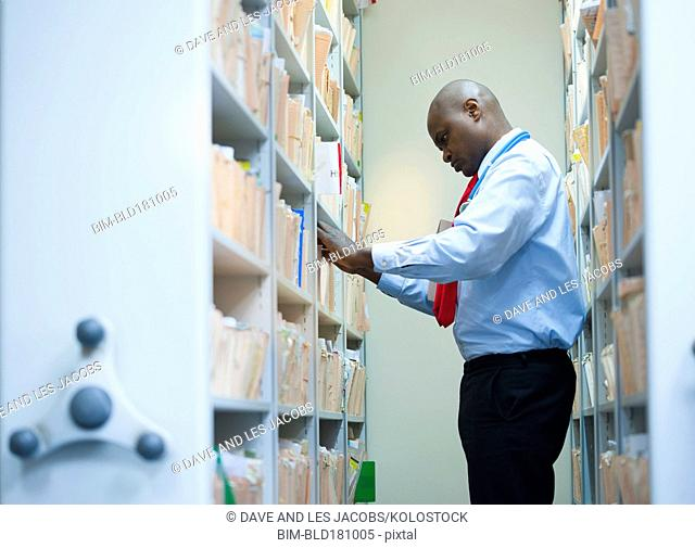 Black businessman filing papers in office