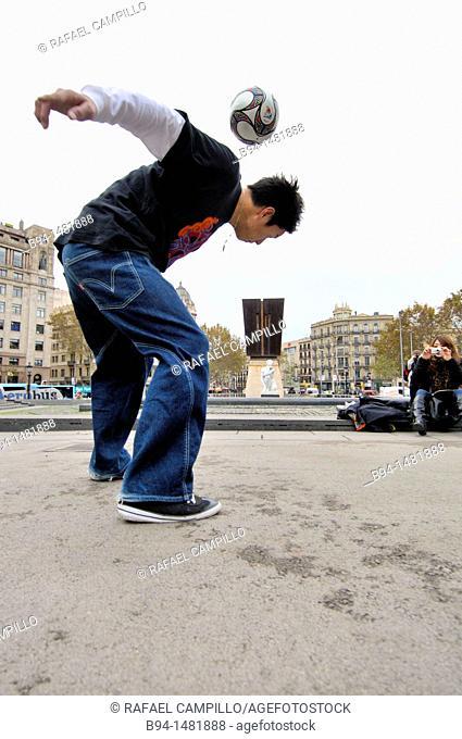 Boy playing with a ball, Plaça de Catalunya, Barcelona, Catalonia, Spain
