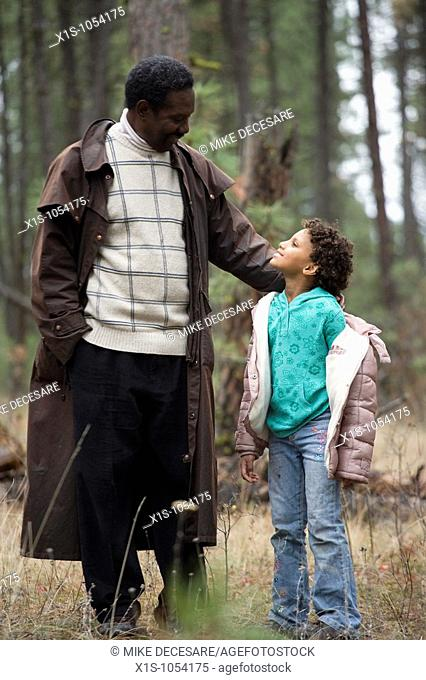 African American Father and Daughter, young child, enjoy each other's company walking through a forest with the little girl stopping to look up at her father