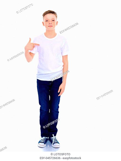 A school-age boy points his fingers at his white T-shirt, on which you can make any inscription. The concept of advertising products, clothing design